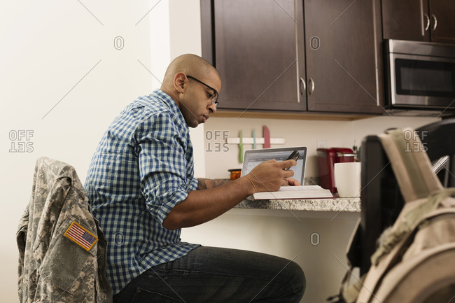 Mixed race soldier using laptop and cell phone on counter