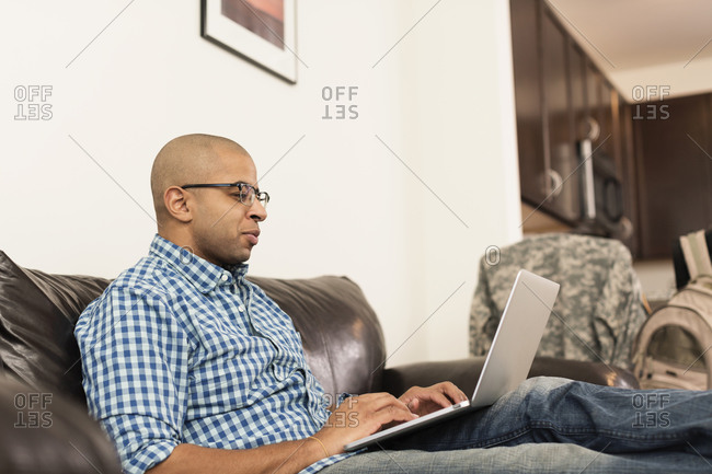 Mixed race man using laptop on sofa in living room