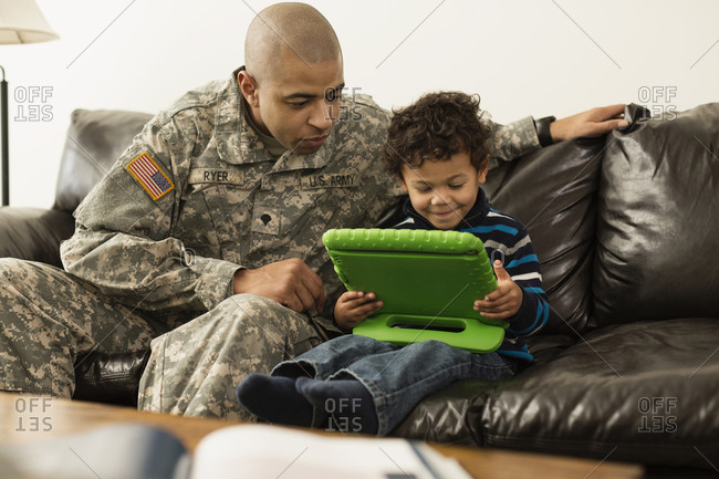 Mixed race soldier father and son using digital tablet on sofa
