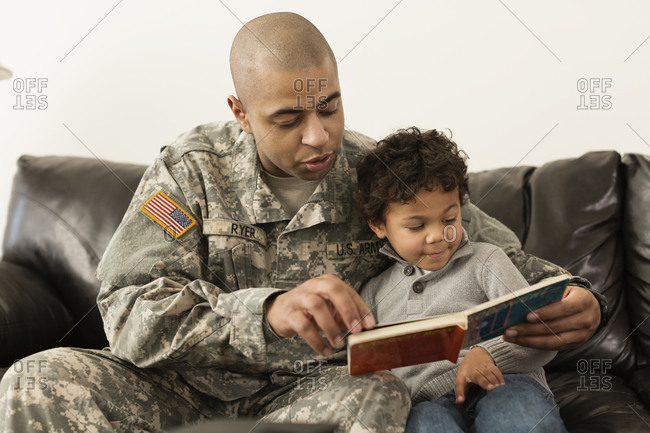 Mixed race soldier reading book to son on sofa