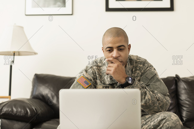 Mixed race soldier using laptop on living room sofa