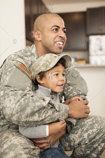 Mixed race soldier father hugging son