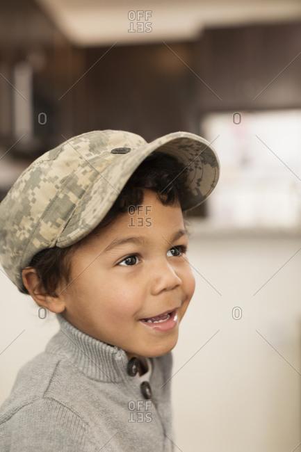 Mixed race boy wearing soldier cap