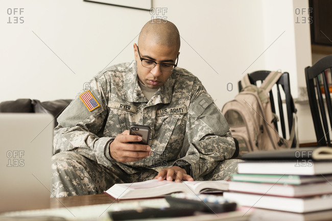 Mixed race soldier texting on cell phone and studying on sofa
