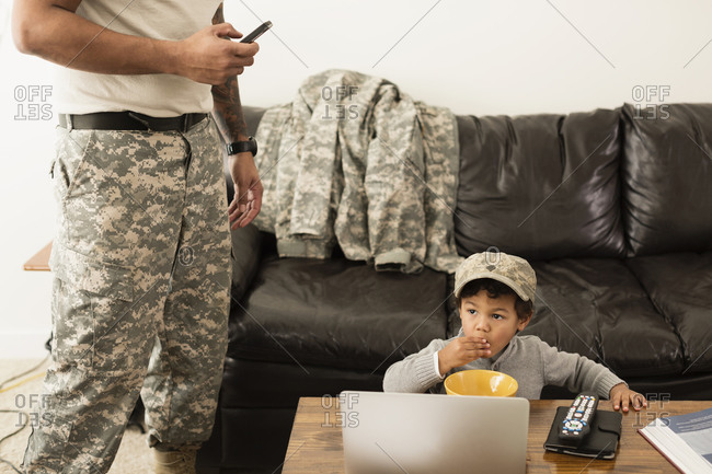 Mixed race father soldier and son relaxing in living room