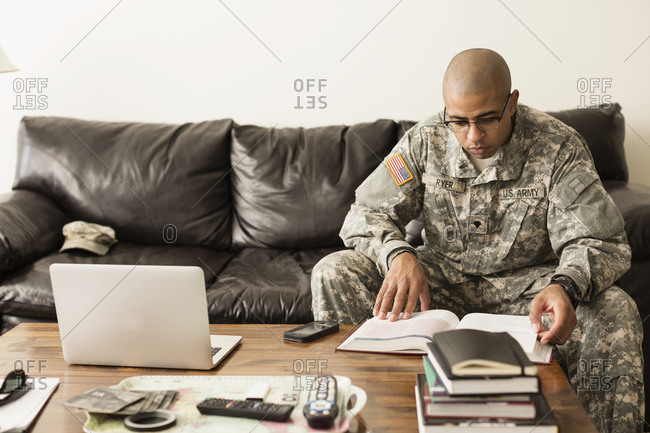 Mixed race soldier studying on sofa