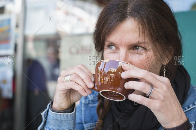 Caucasian woman drinking cup of coffee outdoors
