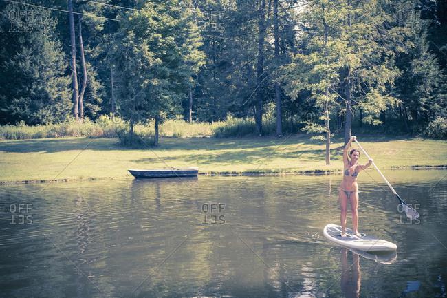 Caucasian woman paddleboarding in lake