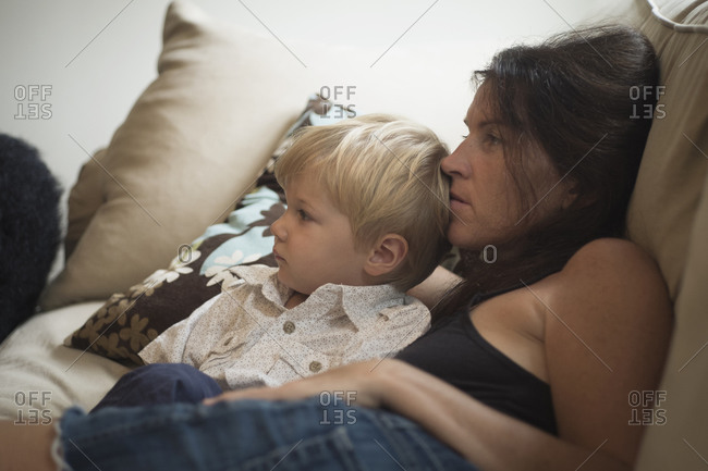 Caucasian mother and son watching television