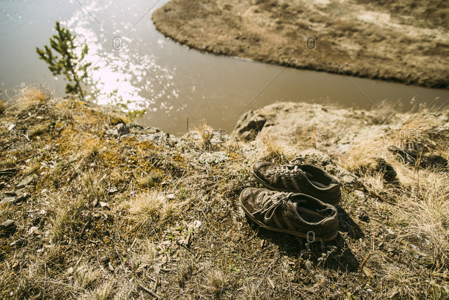 Close up of abandoned shoes over remote river