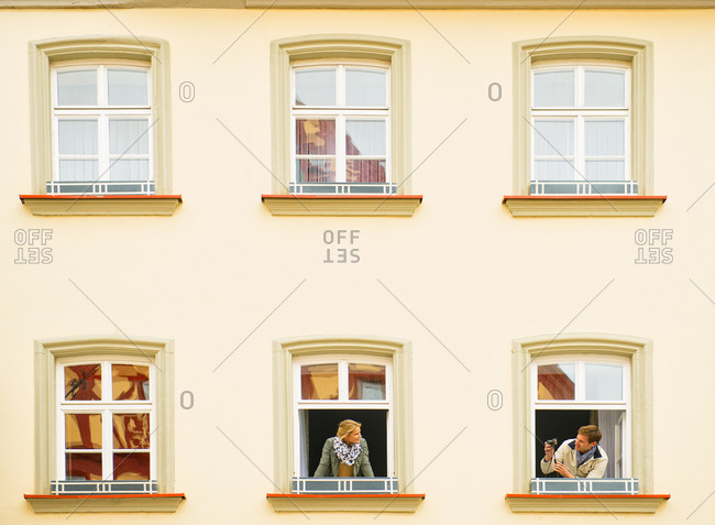 Caucasian man photographing girlfriend from window