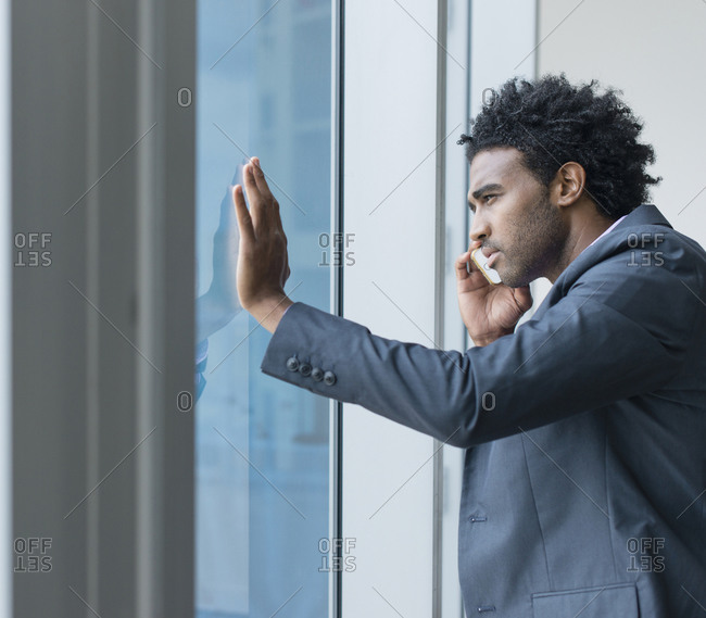 Hispanic businessman talking on cell phone at office window