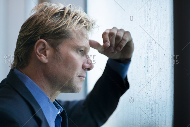 Caucasian businessman standing at rainy office window