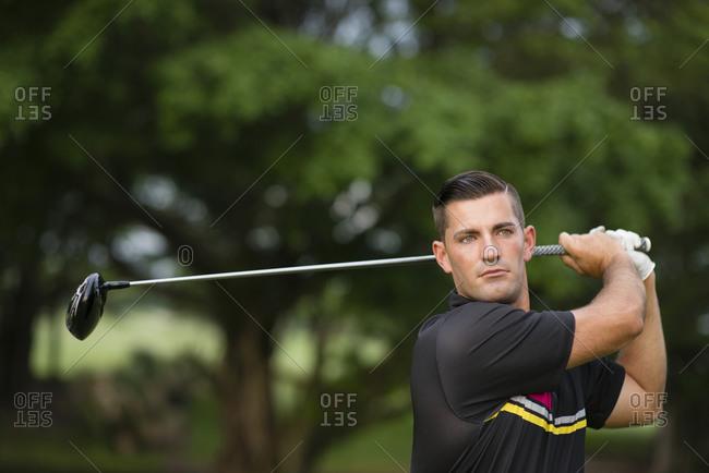 Caucasian man swinging club on golf course
