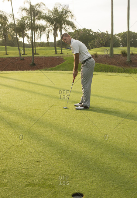Caucasian man putting on golf course