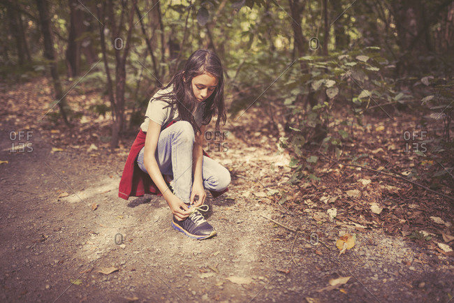 Mixed race girl tying shoelaces on dirt path