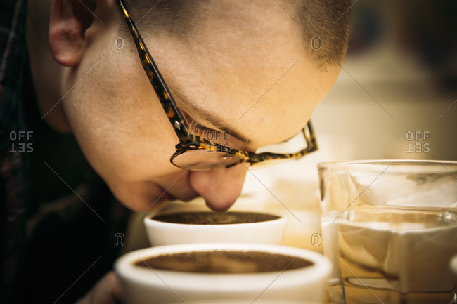 Caucasian barista smelling coffee in cup