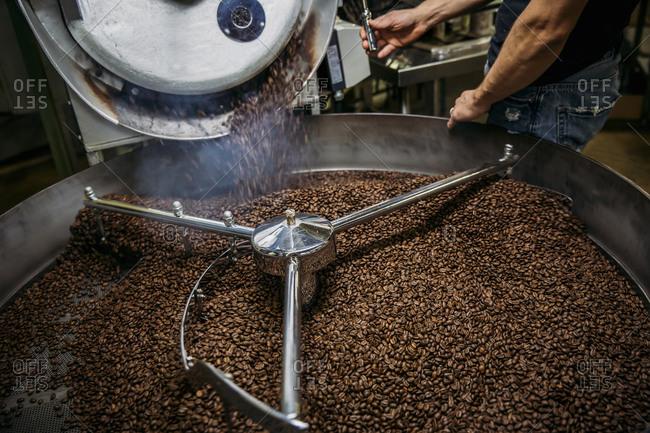 Caucasian roaster working on coffee in machinery