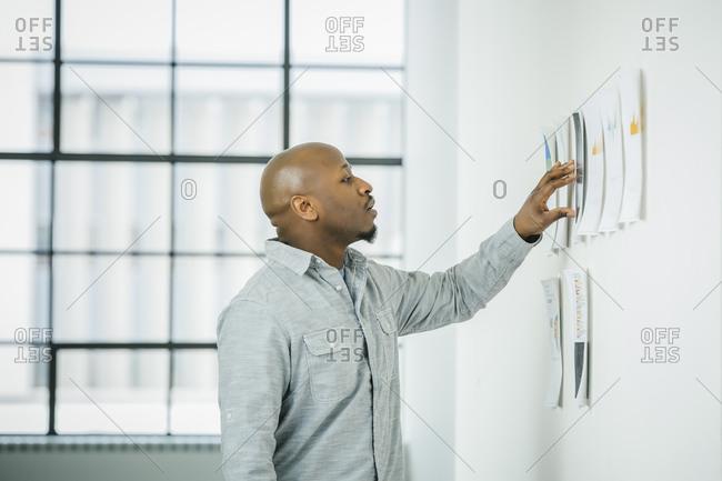 Black businessman examining paperwork on office wall