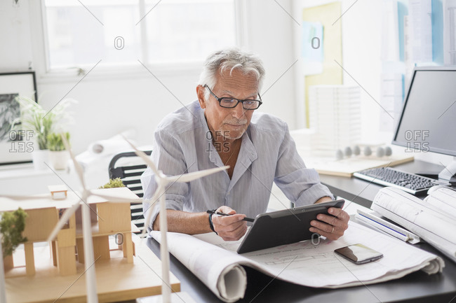 Older Caucasian architect using digital tablet in office