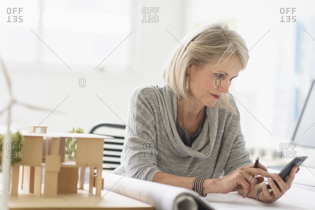 Older Caucasian architect using cell phone in office
