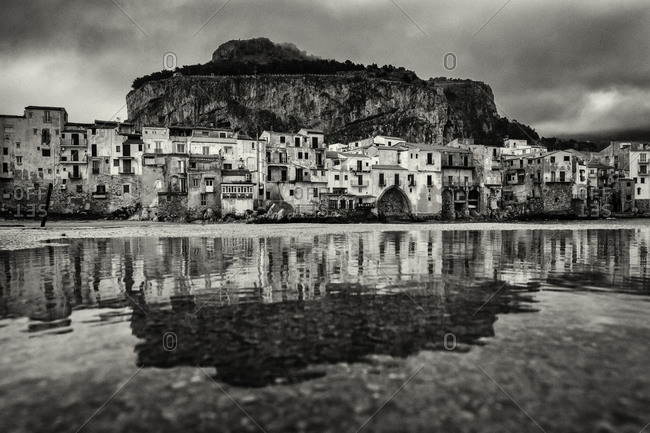 City buildings reflecting in puddle, Cefalu, Palermo, Sicily