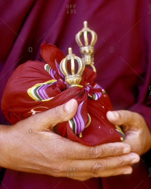 Close up of hands holding ceremonial bells