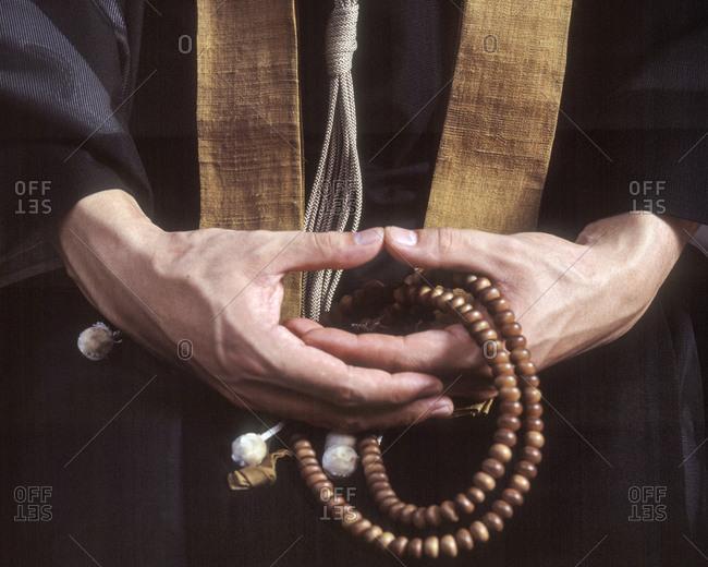 Close up of hands holding Buddhist prayer beads