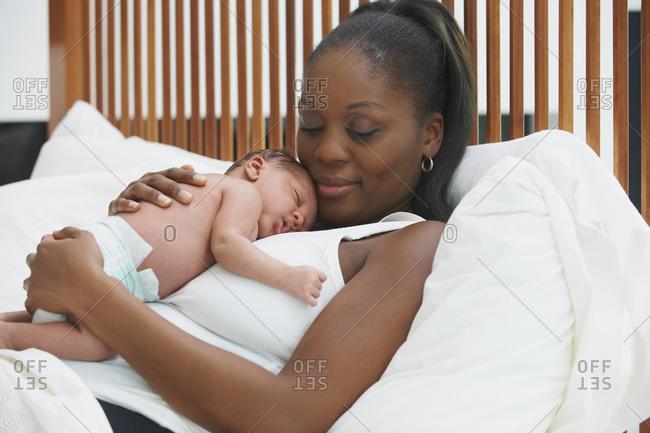 Mother cradling newborn son in bed