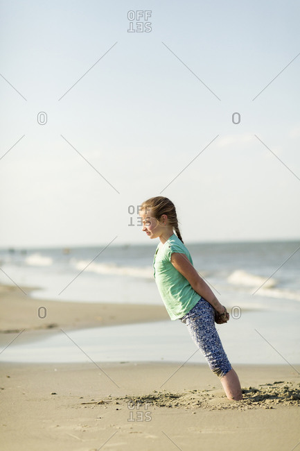 Caucasian girl leaning in sand on beach