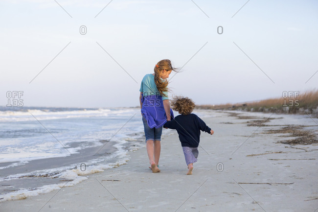 Caucasian brother and sister walking on beach