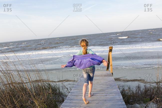 Caucasian girl walking on wooden walkway to beach
