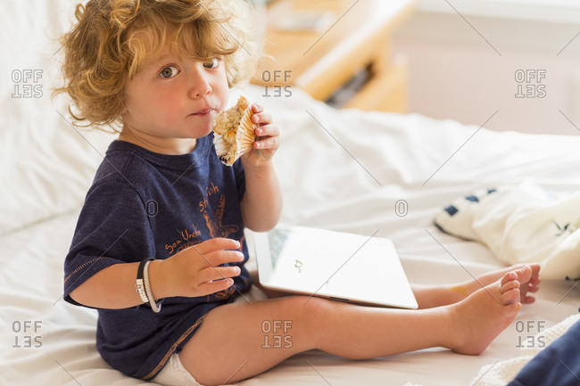 Caucasian baby boy eating and using digital tablet on bed