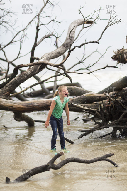 Caucasian girl playing in river near driftwood