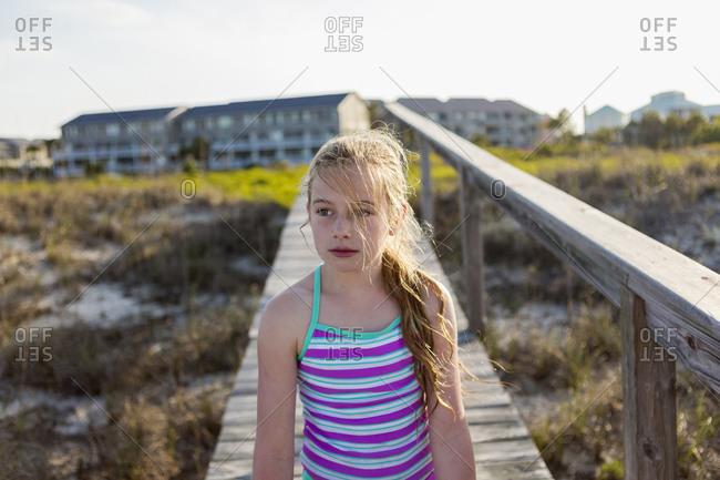 Caucasian girl on wooden walkway on beach