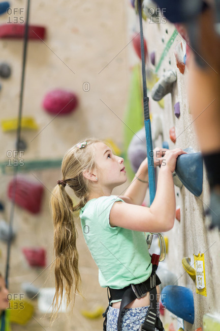 Caucasian girl climbing rock wall indoors
