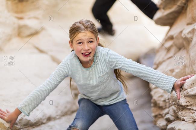 Caucasian girl exploring desert rock formations