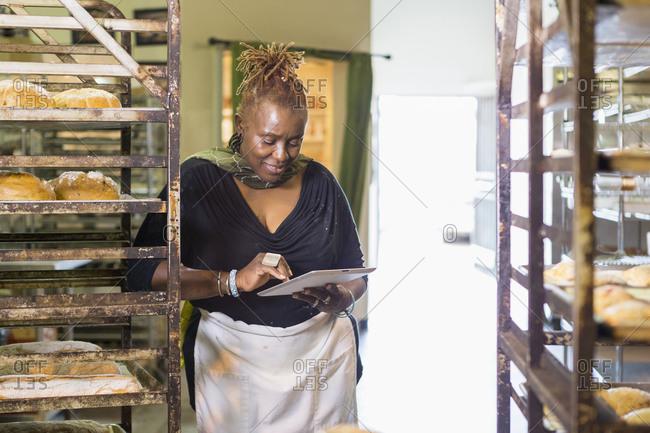 Black baker using digital tablet in bakery kitchen
