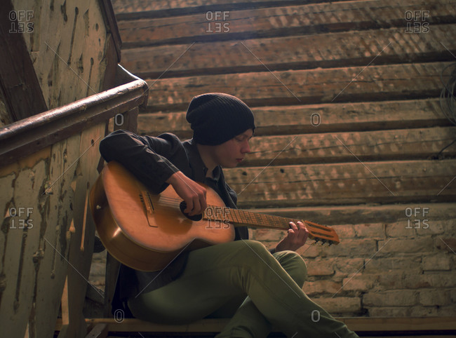 Caucasian man playing guitar on staircase