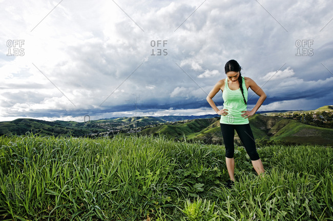 Mixed race athlete standing on rural hilltop