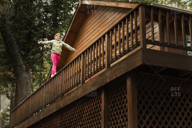 Mixed race girl balancing on balcony banister