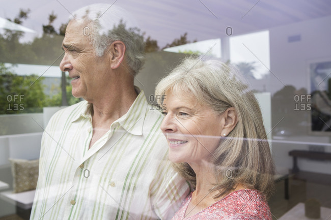 Older Caucasian couple looking out window