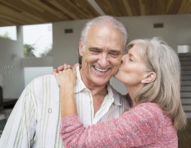 Close up of older Caucasian woman kissing husband