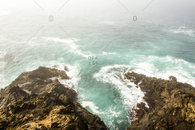 High angle view of ocean waves crashing on cliffs