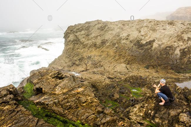 Caucasian hiker sitting on cliffs over ocean, Mendocino, California, United States