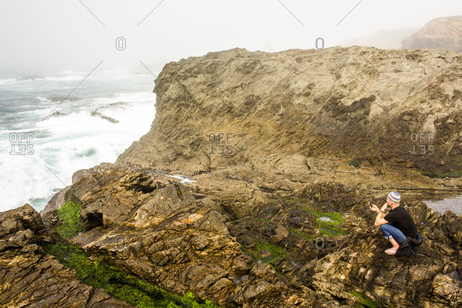 Caucasian hiker sitting on cliffs over ocean, Mendocino, California, United States