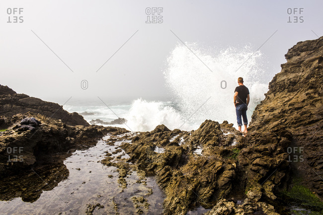 Caucasian hiker watching crashing ocean waves
