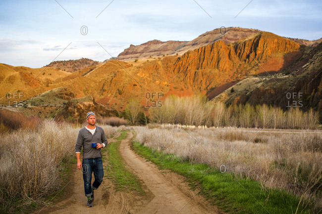 Caucasian man drinking coffee on dirt path, Painted Hills, Oregon, United States