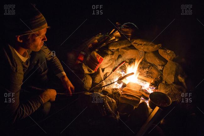 Caucasian man roasting food over campfire