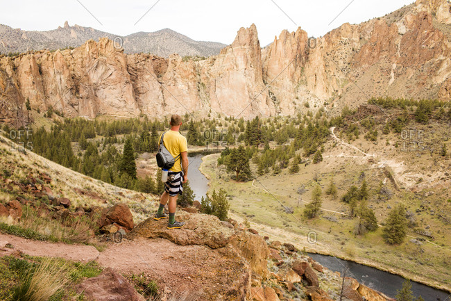 Caucasian hiker admiring hills and stream in desert landscape, Smith Rock State Park, Oregon, United States